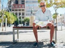 Szczęśliwy starszy męski obsiadanie na ławce z miasto mapą Zdjęcia Royalty Free