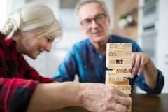 Szczęśliwy starszy małżeństwo bawić się jenga wpólnie zdjęcia royalty free