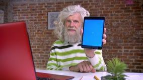 Szczęśliwy stary caucasian mężczyzna z białą wspaniałą brodą i falistym włosy demonstruje błękitnego ekran na jego pastylce podcz