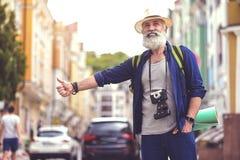 Szczęśliwy stary człowiek łapie taxi w mieście Obraz Royalty Free