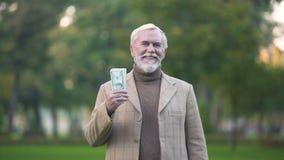 Szczęśliwy stary człowiek trzyma dolarowych rachunki w ręce, emerytuier oszczędzania, fundusz emerytalny zbiory