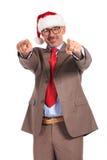 Szczęśliwy starzejący się biznesmen jest ubranym Santa Claus nakrętkę wskazuje jego fing Zdjęcie Royalty Free