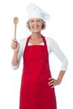 Szczęśliwy starzejący się szef kuchni trzyma drewnianą łyżkę Fotografia Stock