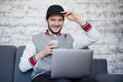 Szczęśliwy studencki facet używa laptop z filiżanka kawy zdjęcia royalty free