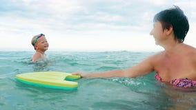 Szczęśliwy syn i macierzysty ono uśmiecha się bawić się z pływanie deski zwolnionym tempem, zdjęcie wideo