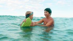 Szczęśliwy syn i macierzysty ono uśmiecha się bawić się z pływanie deski zwolnionym tempem, zbiory
