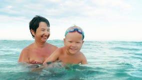 Szczęśliwy syn i macierzysty ono uśmiecha się, patrzejący kamerę robi pluśnięciu w dennym zwolnionym tempie zbiory