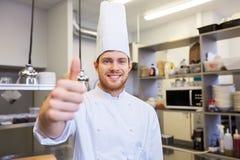 Szczęśliwy szef kuchni przy restauracyjną kuchnią pokazuje aprobaty Obrazy Royalty Free