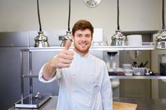 Szczęśliwy szef kuchni przy restauracyjną kuchnią pokazuje aprobaty Obrazy Stock
