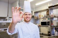 Szczęśliwy szef kuchni przy restauracyjną kuchnią pokazuje ok znaka Fotografia Stock