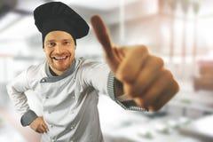 Szczęśliwy szef kuchni z kciukiem przy w górę restauracyjnej kuchni obraz royalty free