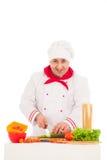 Szczęśliwy szefa kuchni kucharstwo z świeżymi warzywami jest ubranym czerwień i biel Zdjęcia Stock