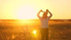 Szczęśliwy tata znosi dziecka obsiadanie na jego ramionach, przy zmierzchem złoty słońce i śmiech swobodny ruch zdjęcie wideo