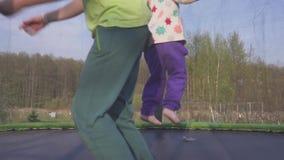 Szczęśliwy trzy roczniaka dziewczyny doskakiwanie na trampoline Emocjonalny radosny portret swobodny ruch zbiory
