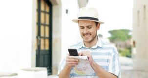 Szczęśliwy turysta wyszukuje telefon zawartość w ulicie zdjęcie wideo