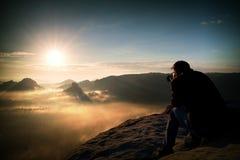 Szczęśliwy turysta z kamerą w rękach siedzi na szczycie piaskowa dopatrywanie, skała w i kolorową mgłę i mgłę w ranek dolinie obraz royalty free