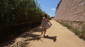 Szczęśliwy turystyczny kobieta spacer wzdłuż historycznej kasztel ściany, Barcelona, Hiszpania zbiory