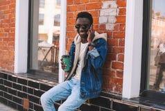 Szczęśliwy uśmiechnięty afrykański mężczyzna wzywa smartphone obsiadanie z filiżanką na miasto ulicie, ściana z cegieł zdjęcia royalty free