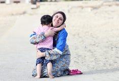 Szczęśliwy uśmiechnięty arabski muzułmański macierzysty ściska jej dziewczynki Zdjęcia Stock