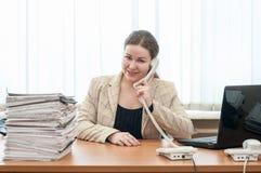 Szczęśliwy uśmiechnięty biurowy pomocniczy obsiadanie przy biurkiem i dzwonić telefonem Zdjęcie Royalty Free