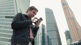 Szczęśliwy uśmiechnięty biznesmen jest ubranym kostium i używa nowożytnego smartphone blisko biura przy wczesnym porankiem, pomyś zbiory wideo