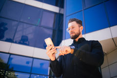 Szczęśliwy uśmiechnięty biznesmen używa nowożytnego smartphone blisko biura, pomyślna pracodawca robić transakci podczas gdy stoj Zdjęcia Royalty Free