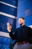Szczęśliwy uśmiechnięty biznesmen używa nowożytnego smartphone blisko biura, pomyślna pracodawca robić transakci podczas gdy stoj Zdjęcie Royalty Free