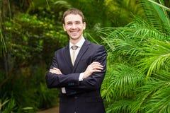 Szczęśliwy uśmiechnięty biznesmen w garniturze w palmowym ogródzie zdjęcia royalty free