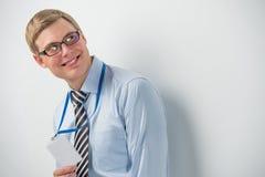 Szczęśliwy uśmiechnięty biznesowy mężczyzna pokazuje pustą odznakę, podczas gdy opierający na ścianie Fotografia Stock