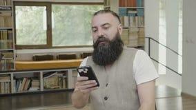Szczęśliwy uśmiechnięty biznesowy mężczyzna z brody odświętności zwycięstwem po scrolling jego mądrze telefon przy biurem i sukce zbiory