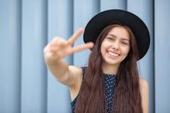 Szczęśliwy uśmiechnięty brunetka model jest ubranym kapelusz i smokingowego pokazuje pokoju znaka z ona palce Przestrzeń dla teks zdjęcia royalty free