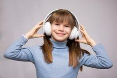 Szczęśliwy uśmiechnięty dziecko cieszy się słucha muzyka w hełmofonach obraz royalty free