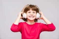 Szczęśliwy uśmiechnięty dziecko cieszy się słucha muzyka w hełmofonach nad bielem obraz stock