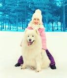 Szczęśliwy uśmiechnięty dziecko i białego Samoyed psia bawić się zima Zdjęcia Royalty Free