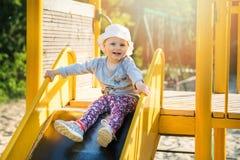 Szczęśliwy uśmiechnięty dziecko na suwaku przy plenerowym boiskiem obraz stock