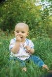 Szczęśliwy, uśmiechnięty dziecko na zielonej trawie, Obrazy Royalty Free