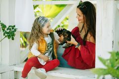 Szczęśliwy uśmiechnięty dziecko odziewa z ślicznymi szczeniakami Yorkshire terier dziewczyna z jej ładną mamą jest ubranym modę c Fotografia Royalty Free