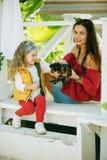 Szczęśliwy uśmiechnięty dziecko odziewa z ślicznymi szczeniakami Yorkshire terier dziewczyna z jej ładną mamą jest ubranym modę c Obrazy Stock