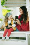 Szczęśliwy uśmiechnięty dziecko odziewa z ślicznymi szczeniakami Yorkshire terier dziewczyna z jej ładną mamą jest ubranym modę c Obraz Stock