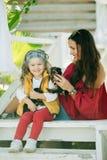 Szczęśliwy uśmiechnięty dziecko odziewa z ślicznymi szczeniakami Yorkshire terier outdoors dziewczyna z jej mamą jest ubranym mod Obrazy Stock