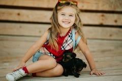 Szczęśliwy uśmiechnięty dziecko odziewa z ślicznymi szczeniakami Yorkshire terier outdoors dziewczyna jest ubranym modę Obrazy Royalty Free