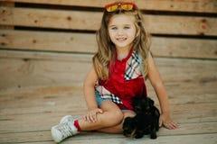 Szczęśliwy uśmiechnięty dziecko odziewa z ślicznymi szczeniakami Yorkshire terier outdoors dziewczyna jest ubranym modę Zdjęcia Stock