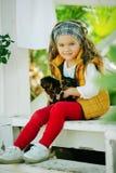 Szczęśliwy uśmiechnięty dziecko odziewa z ślicznymi szczeniakami Yorkshire terier outdoors dziewczyna jest ubranym modę ciepłą Zdjęcia Royalty Free