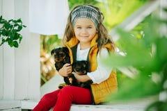 Szczęśliwy uśmiechnięty dziecko odziewa z ślicznymi szczeniakami Yorkshire terier outdoors dziewczyna jest ubranym modę ciepłą Obraz Stock