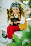 Szczęśliwy uśmiechnięty dziecko odziewa z ślicznymi szczeniakami Yorkshire terier outdoors dziewczyna jest ubranym modę ciepłą Obrazy Stock