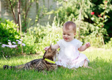 Szczęśliwy uśmiechnięty dziecko w sukni bawić się z kotem w ogródzie Obraz Stock