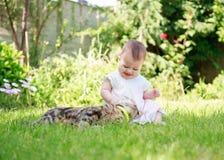 Szczęśliwy uśmiechnięty dziecko w sukni bawić się z kotem w ogródzie Fotografia Stock