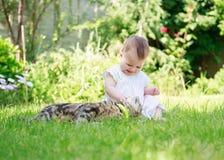 Szczęśliwy uśmiechnięty dziecko w sukni bawić się z kotem w ogródzie Zdjęcia Stock