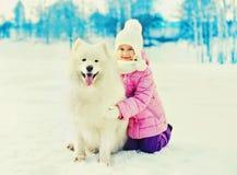 Szczęśliwy uśmiechnięty dziecko z białą Samoyed psa zimą fotografia royalty free