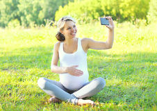 Szczęśliwy uśmiechnięty kobieta w ciąży na trawie i robi autoportretowi na smartphone Obrazy Royalty Free